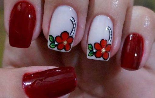 unhas decoradas com esmaltes vermelhos florias